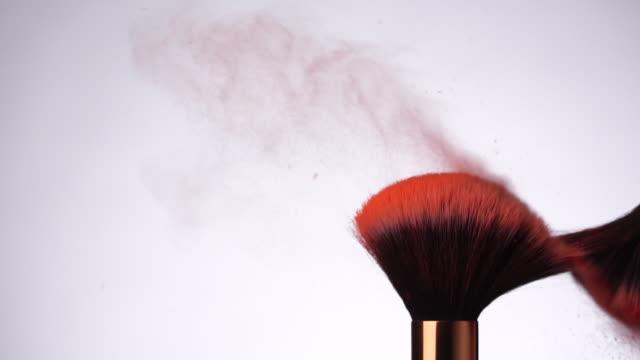 vidéos et rushes de ralenti: pinceau de maquillage de poudre sur fond blanc - maquillage