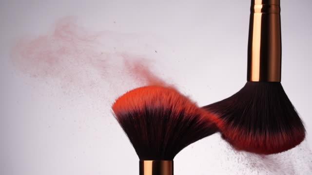 vídeos de stock, filmes e b-roll de slow motion: pincel de maquiagem espalhando pó no fundo branco - pincel