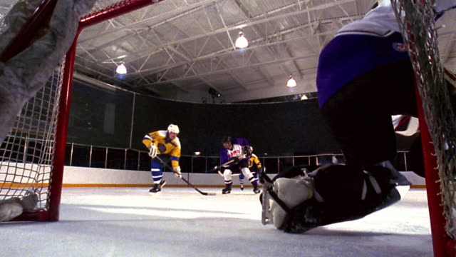 slow motion male hockey player receiving pass + shooting goal as rear view goalie stops puck - tor konstruktion stock-videos und b-roll-filmmaterial
