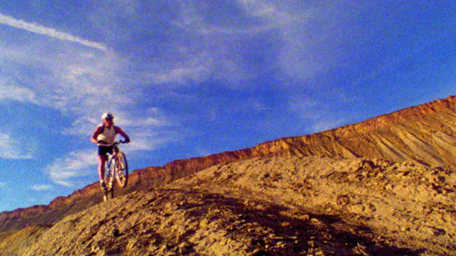 canted slow motion male mountain biker jumping over dirt mound with plateau in background / western colorado - colorado plateau stock videos & royalty-free footage