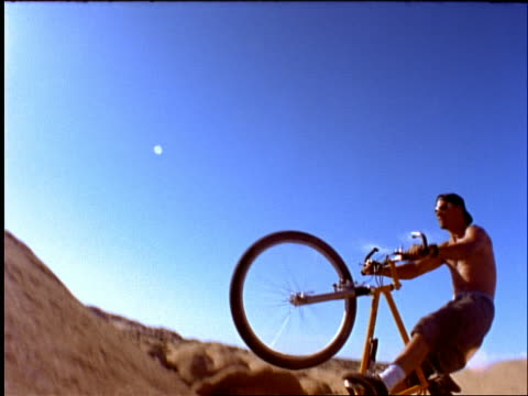vídeos y material grabado en eventos de stock de slow motion male mountain biker riding up rocks + up into air - 1996
