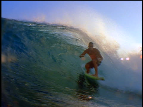 slow motion pan male surfer on surfboard riding in curl of wave past camera - 若い男性だけ点の映像素材/bロール