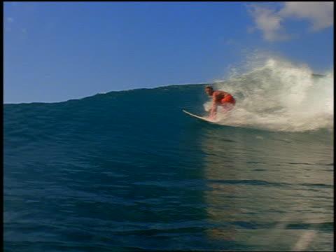 slow motion pan male surfer on surfboard riding wave past camera / wave crashing over camera - 若い男性だけ点の映像素材/bロール