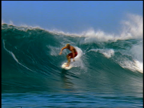 slow motion pan male surfer riding in curl of wave past camera - 若い男性だけ点の映像素材/bロール