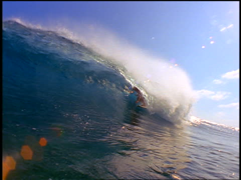 slow motion pan male surfer riding in curl of wave past camera / wave crashing over camera - 若い男性だけ点の映像素材/bロール