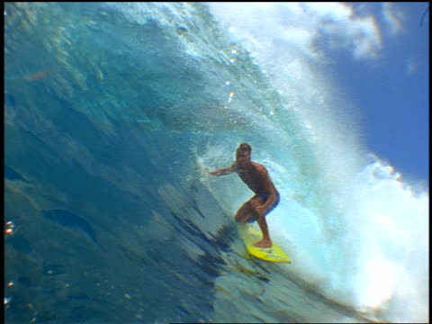 slow motion PAN male surfer with mohawk riding in curl of wave past camera / wave crashing over camera
