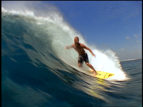 slow motion PAN male surfer with mohawk riding wave past camera / wave crashing over camera