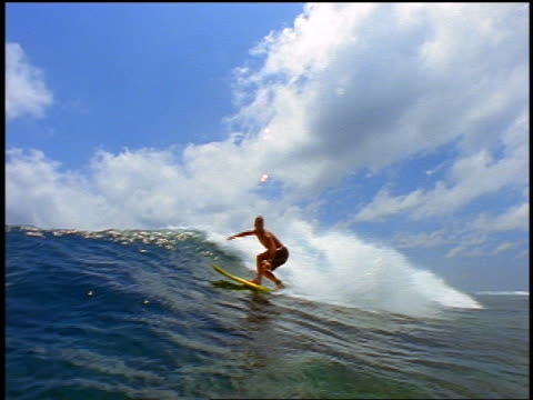slow motion PAN male surfer with mohawk riding wave spraying water at camera