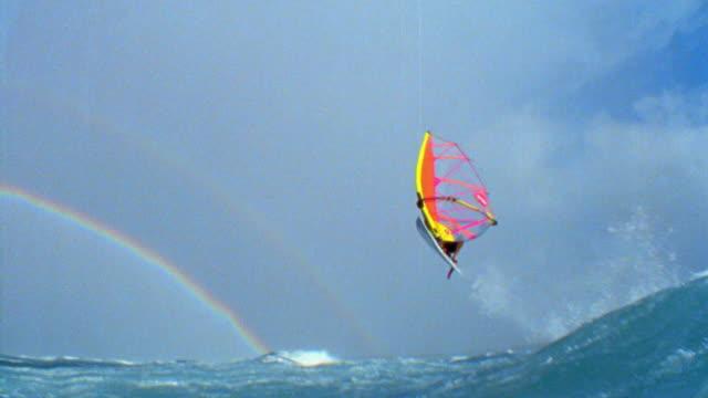 slow motion PAN male windsurfer jumping through air + doing flip / landing by camera / rainbow / Hawaii