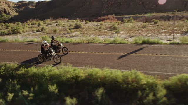 slow motion, man and woman ride motorcycles down desert highway - sandy utah stock videos and b-roll footage