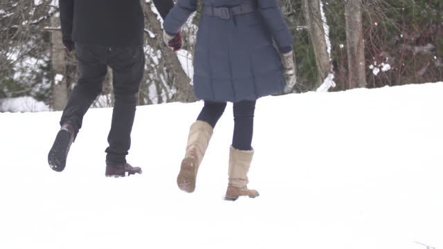 slow motion man and woman walking and stopping on snowy trail and kissing 2 - gemeinsam gehen stock-videos und b-roll-filmmaterial