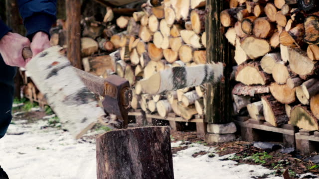 Slow motion: Man chopping wood