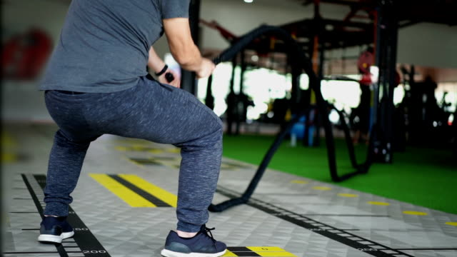 slow motion man doing battle rope exercise at gym - battle stock videos & royalty-free footage
