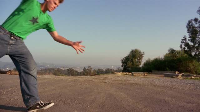 stockvideo's en b-roll-footage met slow motion man doing cartwheel across an empty road - acrobatiek
