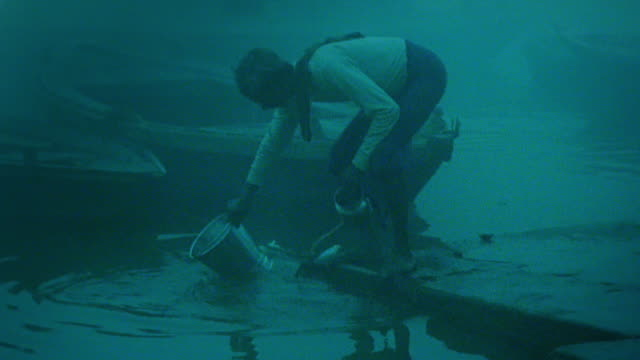 Slow motion man filling bucket with water from Ganges in fog / second man appears and washes cloth /India