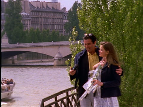 slow motion man gives woman flowers and takes picture by Seine / Paris