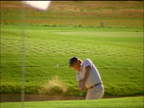 slow motion man hitting golf ball from sand trap onto green / colorado - maglietta polo video stock e b–roll