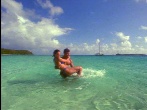 slow motion man holding woman above shallow ocean water turning / sailboat in background / virgin islands - swimwear stock videos and b-roll footage