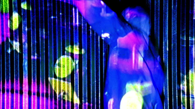 vidéos et rushes de blue slow motion ms man in white hooded jacket dancing with colored shapes projected on him + wall in background - image projetée
