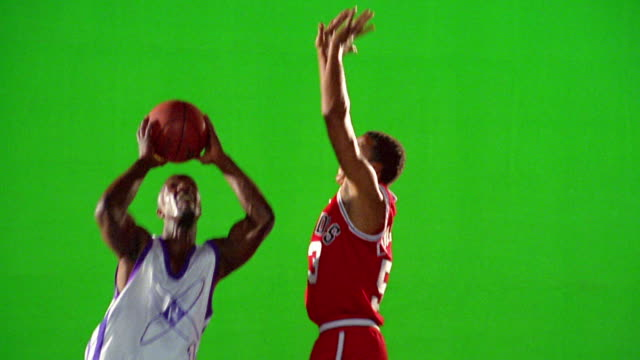 slow motion PAN man in white uniform dribbles past man in red uniform + dunks basketball / green screen