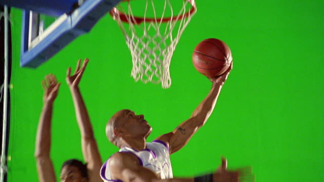 slow motion man in white uniform dunking basketball as man in red uniform tries to block / green screen