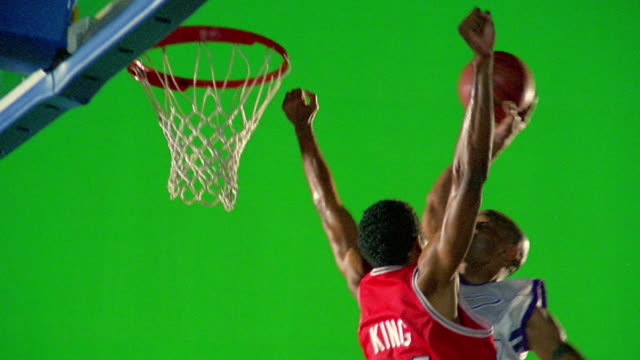 slow motion man in white uniform dunking basketball as man in red uniform tries to block / green screen - defending stock videos & royalty-free footage