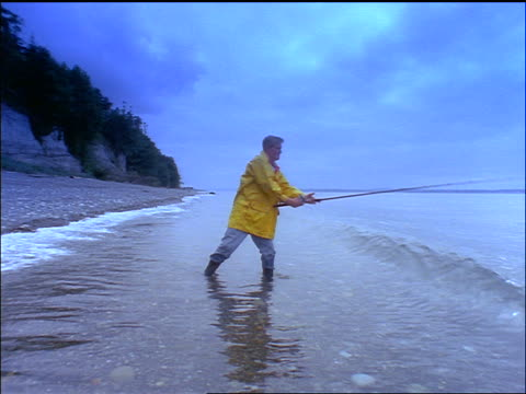 vídeos de stock, filmes e b-roll de slow motion man in yellow raincoat fishing in surf of ocean on grey day / reels in / puget sound, wa - pacífico norte