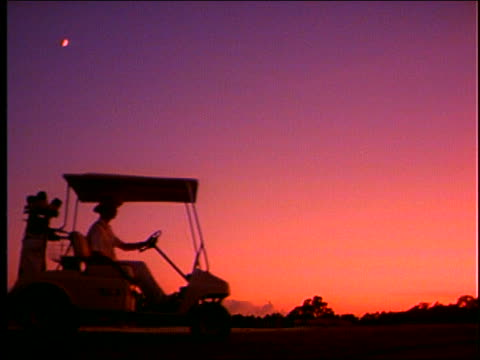 slow motion man on golf cart passing at twilight - golf cart stock videos & royalty-free footage