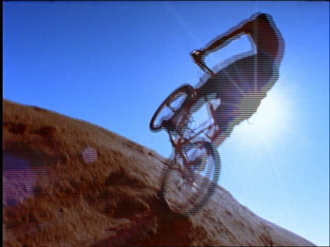 vídeos y material grabado en eventos de stock de slow motion man on mountain bike jumping into air on rocks / sun in background - 1996