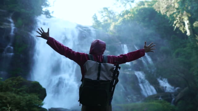 slow motion: man out stretching his hand in front of waterfall - arms raised stock videos & royalty-free footage