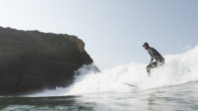 slow motion, man rides wave on surfboard - surfboard stock videos and b-roll footage