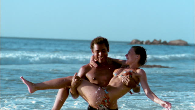 vídeos de stock e filmes b-roll de slow motion man running and carrying smiling woman in bikini out of surf - tronco nu