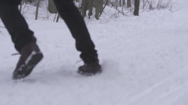 slow motion man running and skids to a stop in the snow in front of woman - 横滑り点の映像素材/bロール