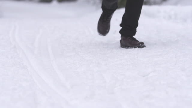 slow motion man running and skids to a stop in the snow - 横滑り点の映像素材/bロール