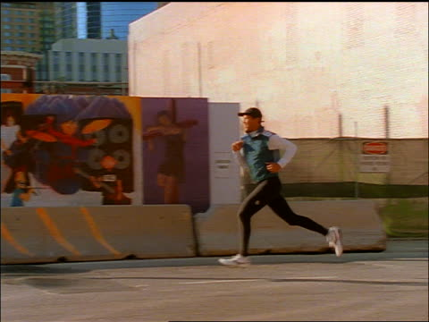slow motion PAN man running past graffiti + construction / Denver, Colorado