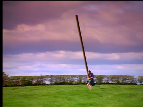 slow motion pan man running + throwing caber on grassy field / caber landing on end + falling / scotland - highland games stock videos & royalty-free footage
