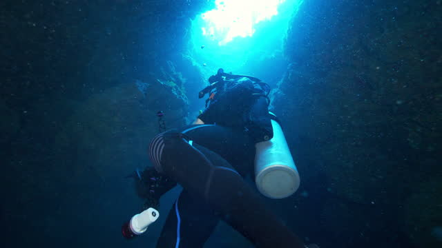 slow motion: man scuba diving while exploring cave undersea - belize city, belize - aqualung diving equipment stock videos & royalty-free footage