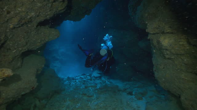 slow motion: man scuba diving while exploring undersea cave - belize city, belize - aqualung diving equipment stock videos & royalty-free footage