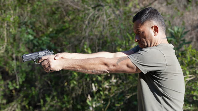 slow motion man shooting a hand gun outdoors - one man only stock videos & royalty-free footage