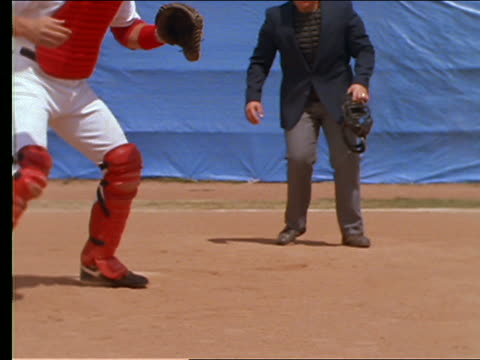 vídeos de stock e filmes b-roll de slow motion man sliding into base as catcher catches ball - camisola de basebol