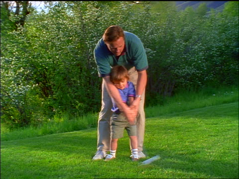 canted slow motion man teaching small boy to swing golf club - golf swing on white stock videos & royalty-free footage
