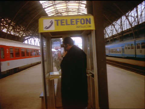 slow motion man using telephone booth on platform in Prague central train station / Czech Republic