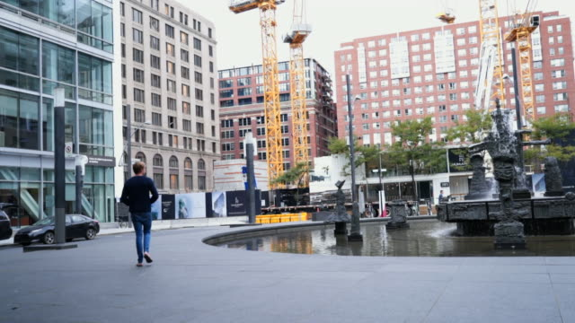 slow motion: man walking past fountain surrounded by high-rise buildings - montréal点の映像素材/bロール