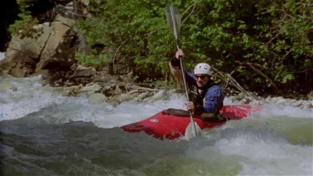 Slow motion man whitewater kayaking down creek and paddling through rapids / Lake Creek, Colorado Rockies