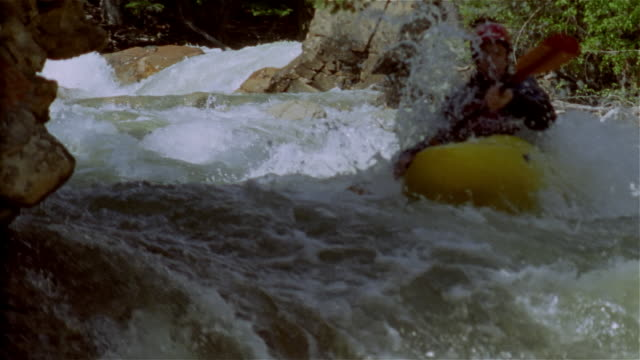 Slow motion man whitewater kayaking down creek and paddling through rapids / Lake Creek, Colorado Rockies
