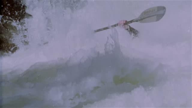 Slow motion man whitewater kayaking down creek and paddling through extreme rapids / Lake Creek, Colorado Rockies