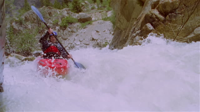 Slow motion man whitewater kayaking down creek and paddling through extreme rapids / Lake Creek, Colorado Rockies