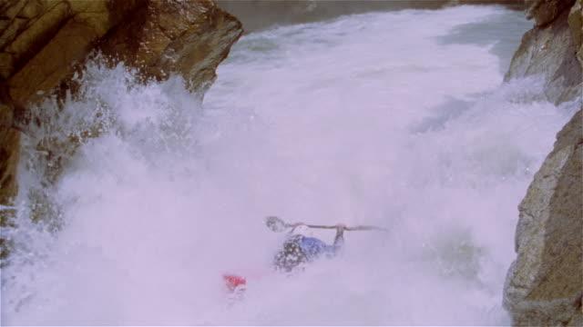 Slow motion man whitewater kayaking down waterfall amongst extreme rapids / kayak flipping over at base of waterfall / Lake Creek, Colorado Rockies
