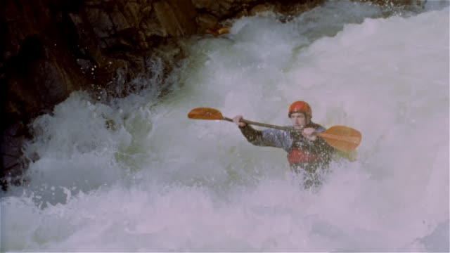 Slow motion man whitewater kayaking down waterfall and paddling through rapids / Lake Creek, Colorado Rockies