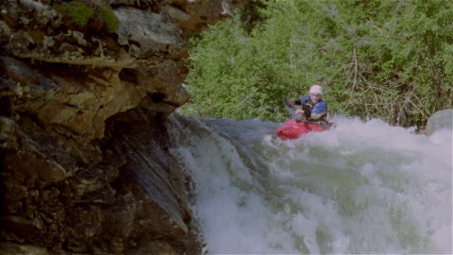 Slow motion man whitewater kayaking down waterfall and paddling through rapids / Lake Creek, Colorado Rockies